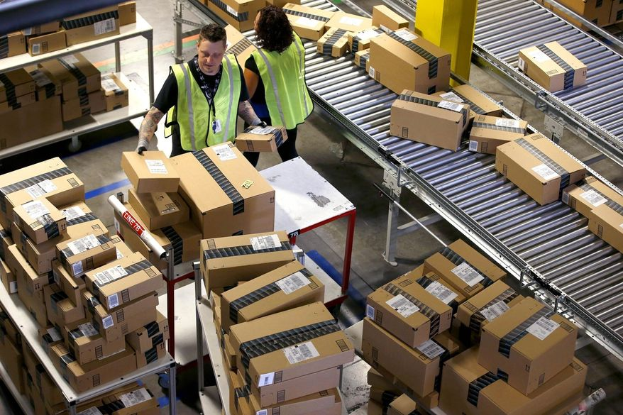 """FILE - In this Dec. 2, 2013 file photo, Amazon.com employees organize outbound packages at an Amazon.com Fulfillment Center on """"Cyber Monday"""" the busiest online shopping day of the holiday season, in Phoenix. Buying things online could soon get pricier for many people after the U.S. Supreme Court's decision Monday, Dec. 12, 2016 not to get involved in a case that may lead to states collecting billions in lost sales taxes. The court opted not to hear a challenge to a Colorado law requiring internet retailers to notify customers and the state how much they owe in Colorado taxes. (AP Photo/Ross D. Franklin, file)"""