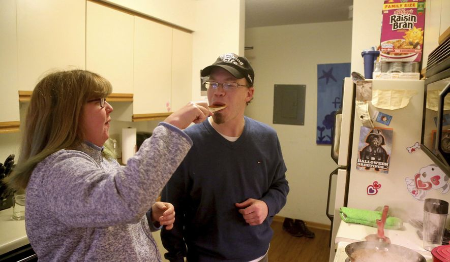 In a Wednesday, Dec. 7, 2016 photo, Steve Allen gets a taste of the sauce from his girlfriend Candace Hanson-Johnson in the apartment Hanson-Johnson shares with her mom, in Eagan, Minn. Allen, 34, who has a cognitive disability, has dreams of one day marrying his sweetheart  Hanson-Johnson, 26. The two have been dating for six years. But Steve's main obstacle is his guardian, who continues to exert broad control over his life. A coalition of Minnesota nonprofits is developing an alternative to a system in which vulnerable adults in the state live under the supervision of a court-appointed guardian who has broad authority over the money, medical care and personal relationships of their wards.  (David Joles/Star Tribune via AP)
