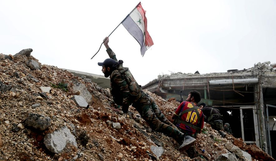 A Syrian soldier places a national flag on the front line with rebel fighters east of Aleppo. Despite the city's fall, the bloody civil war will rage on. (Associated Press)