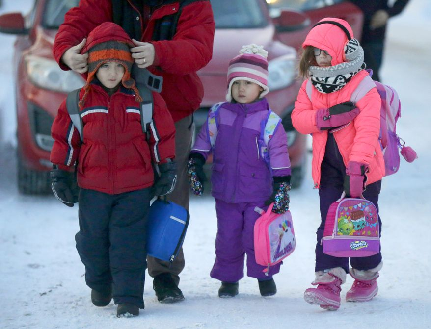 Reese Orr, far left, has his hat secured by his father, Chad Orr, of Milwaukee, as they and Orr's sister, Macy Rea Orr, center, and friend Eleanore Lawton, walk into school at John Greenleaf Whittier Elementary School, in Milwaukee, Wis., on Tuesday, Dec. 13, 2016. Overnight Monday into Tuesday, a blast of arctic air blew into Wisconsin and is dropping temperatures to dangerous levels. The bitterly cold air will settle into southern Wisconsin Tuesday through Friday. (Mike De Sisti  /Milwaukee Journal-Sentinel via AP)