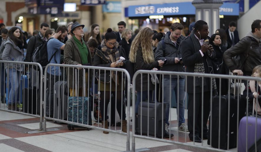 Passengers queue up for an express train to Gatwick Airport, running a reduced service as a result of a train strike, in Victoria rail station London, Tuesday, Dec. 13, 2016.  A 48-hour strike starting Tuesday morning has crippled rail services in southern England as a long-running dispute continues to cause misery for hundreds of thousands of commuters in and out of London. (AP Photo/Matt Dunham)