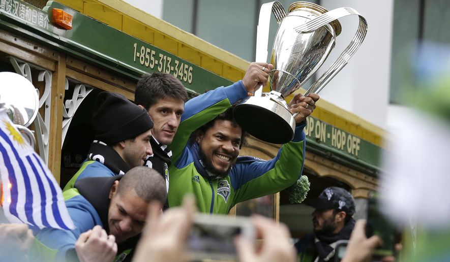 Seattle Sounders' Roman Torres holds the MLS Cup Championship trophy as the team begins a march and rally celebrating their victory, Tuesday, Dec. 13, 2016, in Seattle. Seattle beat Toronto FC 5-4 in a penalty kick shootout Saturday to win their first MLS championship. (AP Photo/Elaine Thompson)
