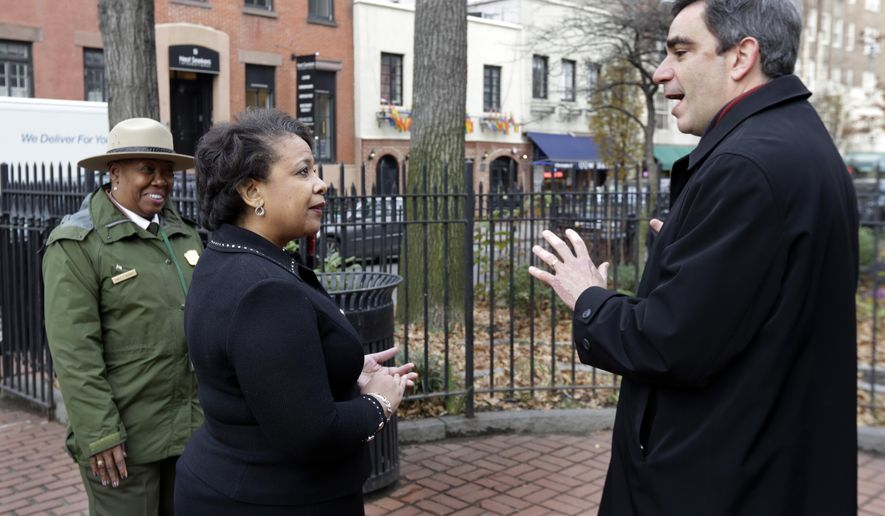 U.S. Attorney General Loretta Lynch, center, talks with National Parks Service Commissioner Joshua Laird, and is accompanied by Superintendent Shirley McKenney, as she visits the new Stonewall National Monument, in New York, Tuesday, Dec. 13, 2016. The monument is adjacent to the Stonewall Inn, background center. (AP Photo/Richard Drew)