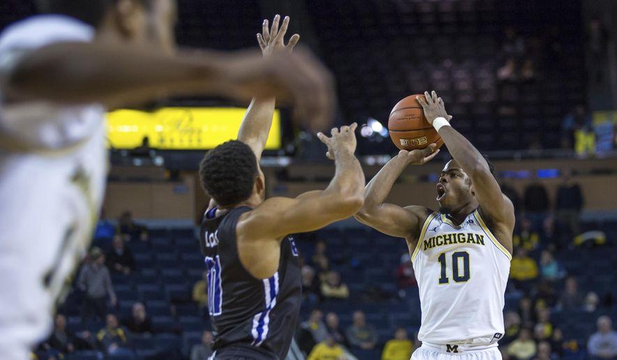 Michigan's Derrick Walton Jr. (10) shoots the ball against Central Arkansas during the first half of an NCAA college basketball game Tuesday, Dec. 13, 2016, in Ann Arbor, Mich. (Matt Weigand/The Ann Arbor News via AP)