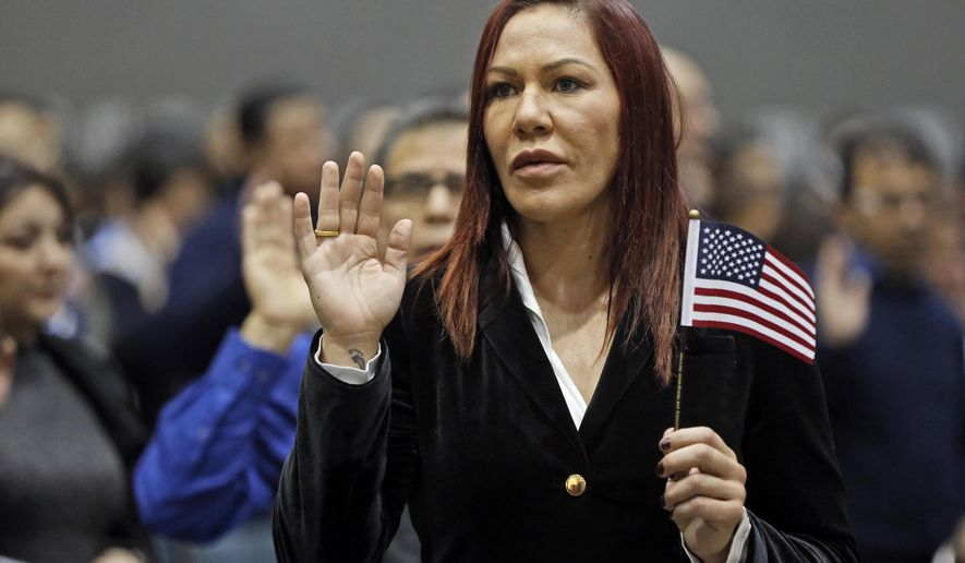 "Brazilian UFC fighter Cris ""Cyborg"" Justino takes the ""Oath of Citizenship"" to become a U.S. citizen during a naturalization ceremony at the Los Angeles Convention Center , Tuesday Dec. 13, 2016. The 31-year-old from Curitaba, Brazil, was among thousands who took the oath. Justino, who said she added Cyborg as a middle name on her naturalization papers, said coming to the United States has changed her life. (AP Photo/Damian Dovarganes)"