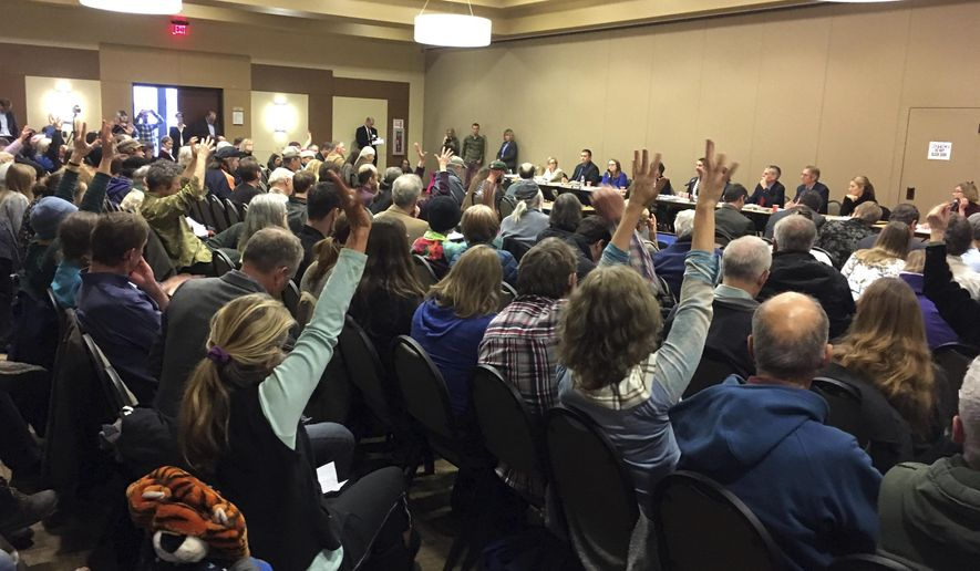 More than 200 people, many waving their hands in silent applause, fill a room at the Keizer Community Center during an Oregon State Land Board meeting Tuesday, Dec. 13, 2016, in Keizer, Ore., as Oregon's top elected state leaders listen to testimony about the proposed sale of the Elliott State Forest. Many oppose the proposal to sell the forest in the Coastal Range to Lone Rock Timber Co. and its partners, including several Indian tribes. (AP Photo/Andrew Selsky)