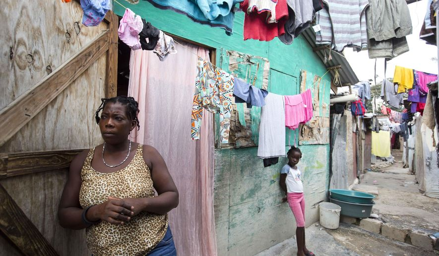 In this Dec. 2, 2016 photo, Adrienne St. Fume stands outside her shelter in the Delmas tent camp set up set up nearly seven years for people displaced by the 2010 earthquake, in Port-au-Prince, Haiti. The mother of three said she figured the shack built of plywood scraps and plastic tarp would be temporary as they and the rest of Port-au-Prince recovered from the earthquake. But St. Fume has yet to find a way out. (AP Photo/Dieu Nalio Chery)