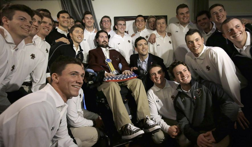 Former Boston College baseball captain Pete Frates, center left, and his brother Andrew, center right, pose for a photo with members of the Boston College baseball team after Pete was presented with the 2017 NCAA Inspiration Award, Tuesday, Dec. 13, 2016, at his home in Beverly, Mass. The NCAA honored Frates who inspired the ice bucket challenge that raised millions of dollars for Lou Gehrig's disease research. Frates was diagnosed with ALS in 2012. (AP Photo/Steven Senne)