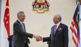 Singapore's Prime Minister Lee Hsien Loong, left, shakes hand with Malaysia's Prime Minister Najib Razak after a press conference in Putrajaya, Malaysia, Tuesday, Dec. 13, 2016. Malaysia and Singapore today signed the long-awaited agreement on the Kuala Lumpur-Singapore High Speed Rail (HSR) project. (AP Photo/Vincent Thian)
