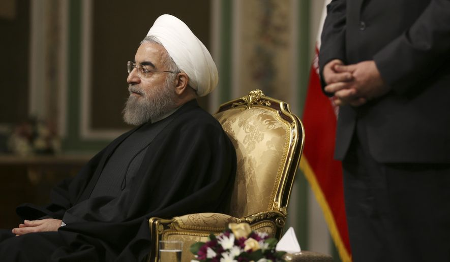 In this picture taken on Tuesday, Nov. 22, 2016, Iranian President Hassan Rouhani sits in a ceremony as his Foreign Minister Mohammad Javad Zarif stands at right at the Saadabad palace in Tehran, Iran. Iran's president on Tuesday ordered officials to draw up plans to build nuclear-powered ships and to show how the United States violated last year's nuclear deal, a response to a vote by the U.S. Congress to extend some sanctions on the country. (AP Photo/Vahid Salemi)
