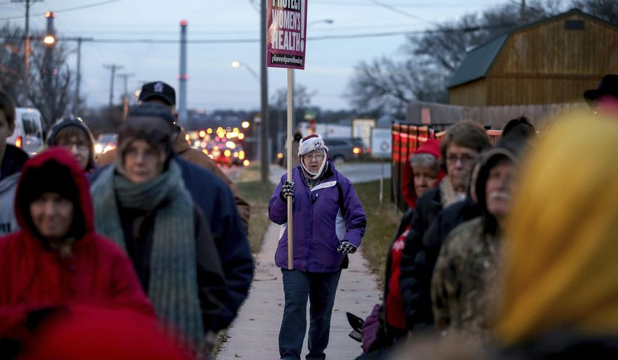 Planned Parenthood supporter Pat Holt walks with a sign through a small crowd that gathered for a news conference by anti-abortion advocates accusing Planned Parenthood facilities of being unsafe outside the Planned Parenthood Columbia Health Center on Monday, Dec. 12, 2016 in Columbia, Mo.  (Timothy Tai/Columbia Daily Tribune via AP)
