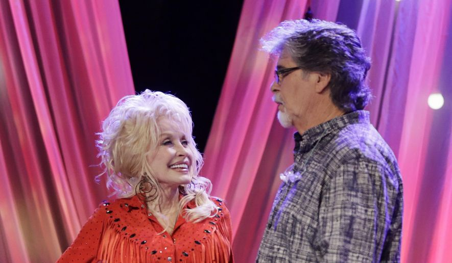 Dolly Parton talks with Randy Owen of the group Alabama during tapings for Parton's Smoky Mountain Rise Telethon Tuesday, Dec. 13, 2016, in Nashville, Tenn. Parton has lined up an all-star list of performers for a three-hour telethon to raise money for thousands of people whose homes were damaged or destroyed in Tennessee wildfires. (AP Photo/Mark Humphrey)