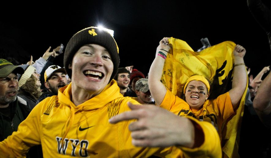 FILE - In this Saturday, Nov. 19, 2016, file photo, Wyoming fans react after the team defeated San Diego State 34-33 in Laramie, Wyo. By all accounts, Wyoming's football program has made a remarkable turnaround from a team that last had a winning season in 2011 and won just two games last year. But Cowboys coach Craig Bohl isn't satisfied with one good year: he wants a program that is a consistent winner over multiple seasons. (AP Photo/Shannon Broderick, File)
