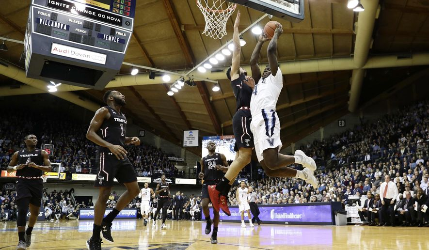 Villanova's Eric Paschall, right, goes up for a shot against Temple's Obi Enechionyia during the first half of an NCAA college basketball game, Tuesday, Dec. 13, 2016, in Villanova, Pa. (AP Photo/Matt Slocum)
