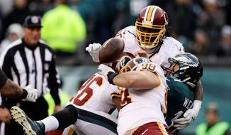 The Washington Redskins' Bashaud Breeland (26), Matthew Ioannidis (98) and Ricky Jean Francois take down Philadelphia Eagles quarterback Carson Wentz in the second half on Sunday. The Redskins kept an opponent from taking the lead late in the fourth quarter or overtime six of seven times this season. (Associated Press)
