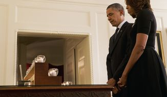 President Barack Obama and first lady Michelle Obama observe a moment of silence in honor of the Newtown shooting victims, in the Map Room of the White House in Washington, Saturday, Dec. 14, 2013, on the one year anniversary of the tragedy. (AP Photo/Jacquelyn Martin)