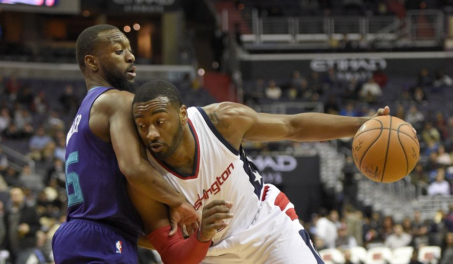 Washington Wizards guard John Wall, right,drives to the basket against Charlotte Hornets guard Kemba Walker, left, during the second half of an NBA basketball game, Wednesday, Dec. 14, 2016, in Washington. The Wizards won 109-106. (AP Photo/Nick Wass)