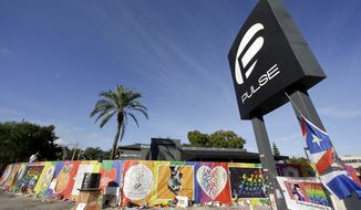 In this Wednesday, Nov. 30, 2016 photo, artwork and signatures cover a fence around the Pulse nightclub, scene of a mass shooting, in Orlando, Fla. (AP Photo/John Raoux)