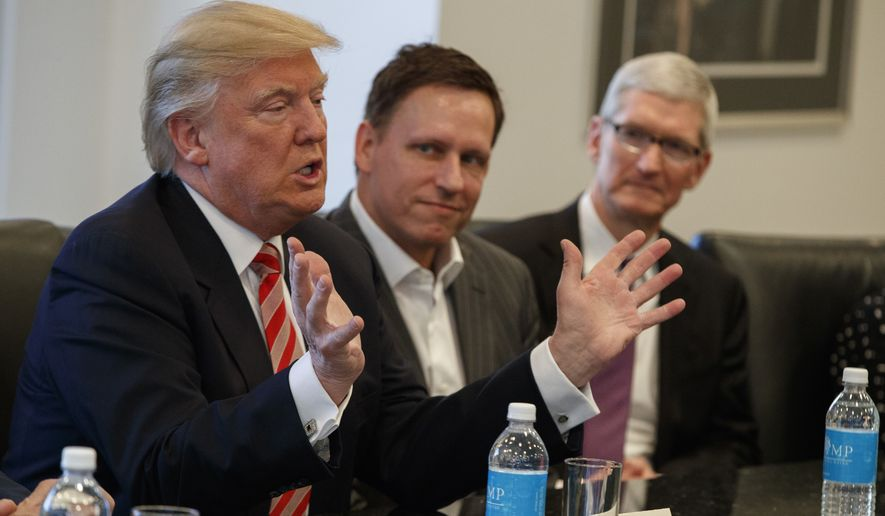 Apple CEO Tim Cook (right) and PayPal founder Peter Thiel listen as President-elect Donald Trump speaks during a meeting with technology industry leaders Wednesday at Trump Tower in New York. (Associated Press)