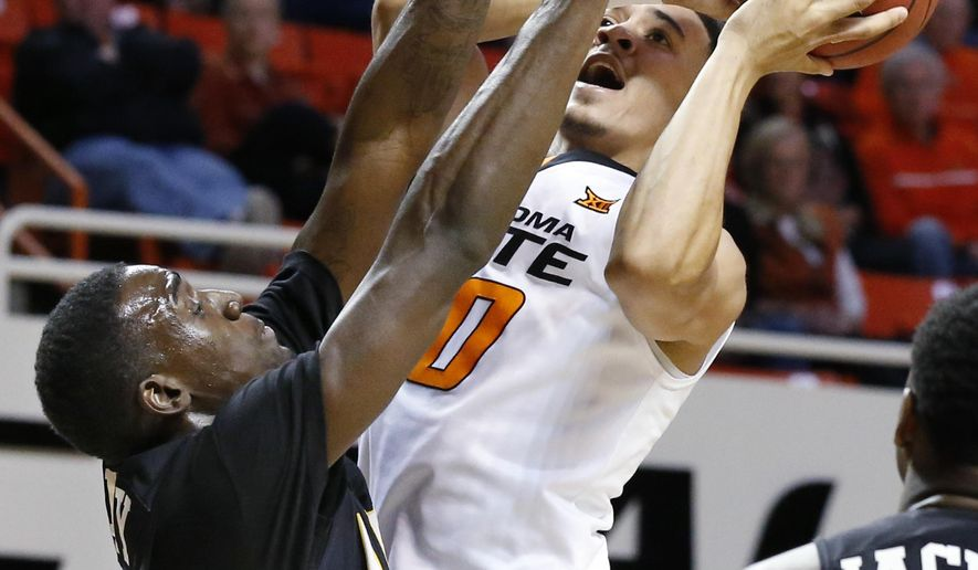 Arkansas-Pine Bluff forward Devin Berry, left, defends as Oklahoma State guard Jeffrey Carroll, right, shoots in the first half of an NCAA college basketball game in Stillwater, Okla., Wednesday, Dec. 14, 2016. (AP Photo/Sue Ogrocki)