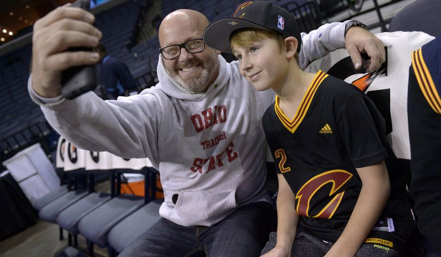 Ohio native Mark Edge takes a photo with his son Coleman Edge, 12, after they were invited by Cleveland Cavaliers security to sit on the team's bench during player warmups before an NBA basketball game between the Cavaliers and the Memphis Grizzlies Saturday, Dec. 10, 2016, in Memphis, Tenn. (AP Photo/Brandon Dill)