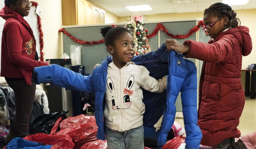 In this Dec. 9, 2016 photo, Gennine Moody, left, watches as her daughters Breonna, center, and Mychayla try on winter coats at the Neighborhood Association for Intercultural Affairs in the Bronx borough of New York. The used coats were donated as part of a collection and distribution effort by the New York Mets and New York Cares. (AP Photo/Mark Lennihan)