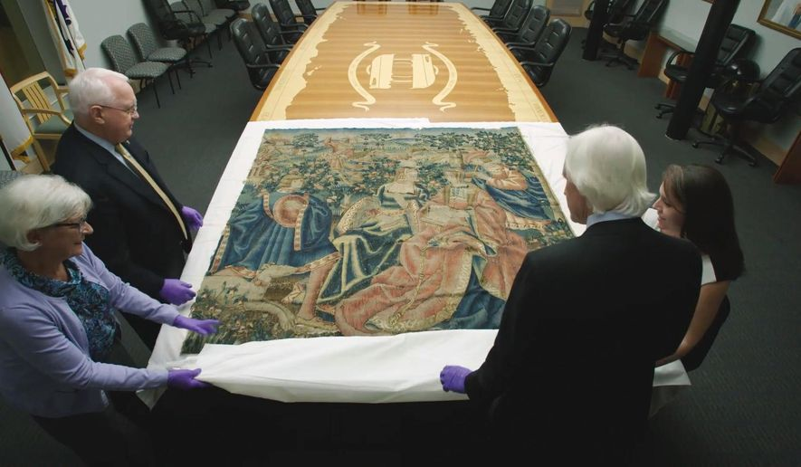 "This Nov. 7, 2016 image from video provided by HISTORY Canada & More4 shows a 16th century tapestry at the National WWII Museum in New Orleans that had been in Adolf Hitler's retreat in the Bavarian Alps. Looking at the tapestry are Dr. Nick Mueller, top left, and Toni Kiser, right, both from the museum, Cathy Hinz, bottom left, the daughter of Lt. Col. Paul Danahy, the American officer who took the tapestry from Hitler's Eagle's Nest in 1945, and Robert Edsel, presenter of the television documentary series ""Hunting Nazi Treasure."" On Friday, Dec. 16, 2016, the tapestry, purchased for Hitler's Eagle's Nest a year before the war began from an art gallery in Munich owned by a Jewish family, will be formally returned to Germany in a ceremony. (HISTORY Canada & More4 via AP)"