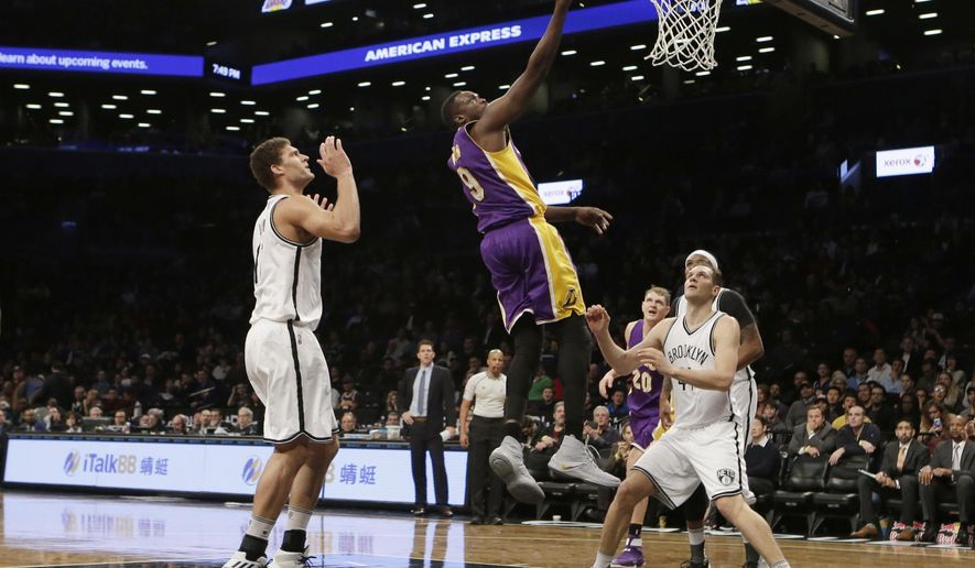 Los Angeles Lakers' Luol Deng (9) drives past Brooklyn Nets' Brook Lopez (11) and Bojan Bogdanovic (44) during the first half of an NBA basketball game, Wednesday, Dec. 14, 2016, in New York. (AP Photo/Frank Franklin II)