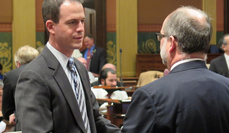 House Speaker Kevin Cotter, R-Mt. Pleasant, speaks with Senate Majority Leader Arlan Meekhof, R-West Olive, on Wednesday, Dec. 14, 2016, in the House chamber in Lansing, Mich. The Legislature was in session late into the night in the final days of the two-year session. (AP Photo/David Eggert)