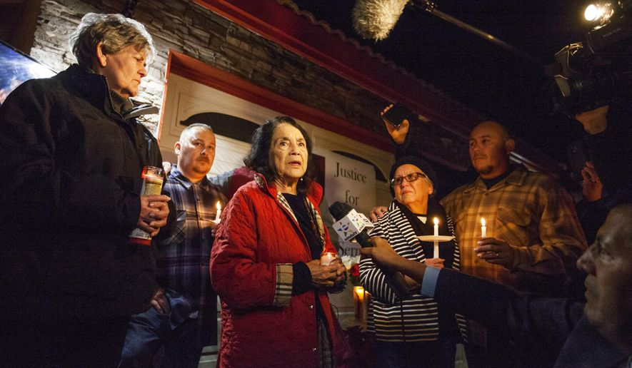 In this photo provided by The Bakersfield Californian, activist Dolores Huerta, center, speaks at a candlelight vigil for Francisco Serna, 73, Tuesday, Dec. 13, 2016, in Bakersfield, Calif. From right are Serna's son Frank Serna, wife Rubia Serna and son Roy Serna. Serna was shot and killed by a Bakersfield, Calif., police officer near his home early Monday. Police Chief Lyle Martin said Tuesday that the unarmed Serna refused to take his hand out of his pocket when he was shot by an officer who thought he had a gun. Serna's family said he suffers from dementia and he often took walks in the evening. (Felix Adamo/The Bakersfield Californian via AP)