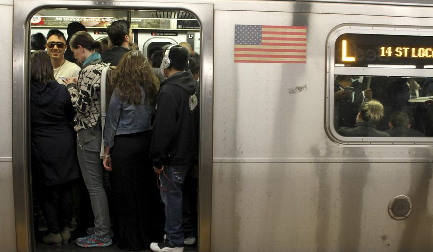 FILE - This May 5, 2016 file photo shows passengers crowd on the L Train subway in the Brooklyn borough of New York. Tourists who decide to try the subways will find them crowded, noisy and confusing, but they are the most efficient way to get around the city.  (AP Photo/William Mathis, File)