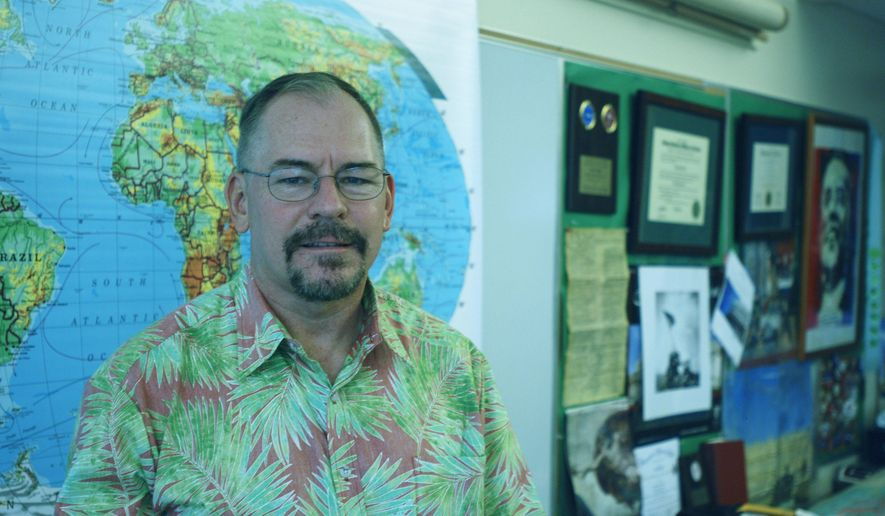 Electoral College elector John Bickel, a Hawaii Democrat, poses in his classroom at Iolani High School on Wednesday, Dec. 14, 2016 in Honolulu. Bickel, who says he plans to vote for Hillary Clinton, recently joined a movement to request information about possible Russian hacking during the presidential election. (AP Photo/Cathy Bussewitz)