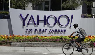 FILE - In this Tuesday, July 19, 2016 file photo, a cyclist rides past a Yahoo sign at the company's headquarters in Sunnyvale, Calif. (AP Photo/Marcio Jose Sanchez)