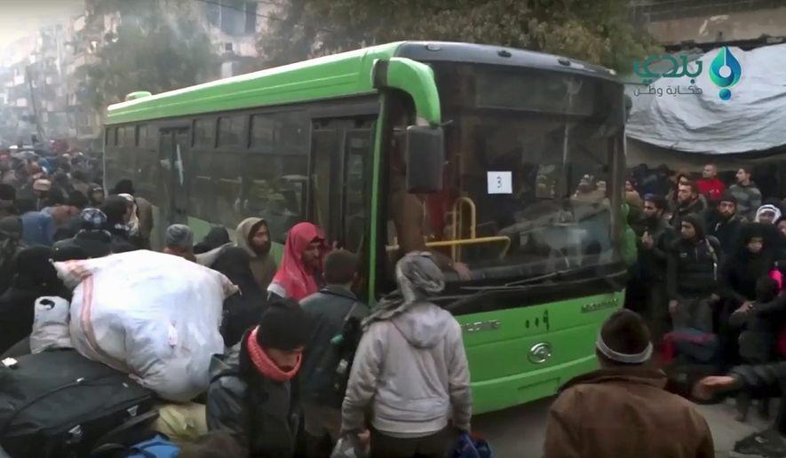 "Buses were sent to the war-torn city of Aleppo to evacuate residents under a cease-fire deal reached with rebels in the wake of a Russian-backed assault that Syrian President Bashar Assad called a successful ""liberation."" (Associated Press)"