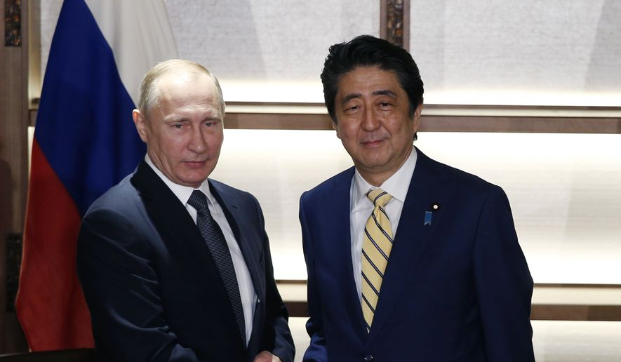 Russia's President Vladimir Putin, left, and Japan's Prime Minister Shinzo Abe shake hands as they pose for photographers at the start of their summit meeting in Nagato, western Japan, Thursday, Dec. 15, 2016. Putin arrived in Japan on Thursday for a two-day summit that marks his first official visit to a G-7 country since Russia's 2014 annexation of Crimea. (Toru Hanai/Pool Photo via AP)