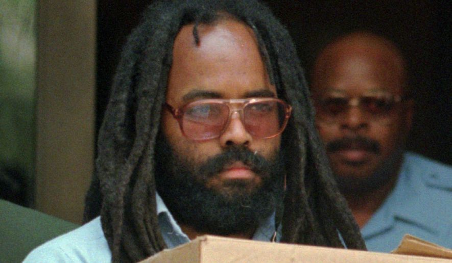 Mumia Abu-Jamal leaves Philadelphia's City Hall after a hearing on July 12, 1995. Abu-Jamal is serving a life term for the 1981 killing of a Philadelphia police officer. (Associated Press)