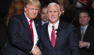 President-elect Donald Trump, left, shakes hands with Vice President-elect Mike Pence during a rally at the Giant Center, Thursday, Dec. 15, 2016, in Hershey, Pa. (AP Photo/Matt Rourke)