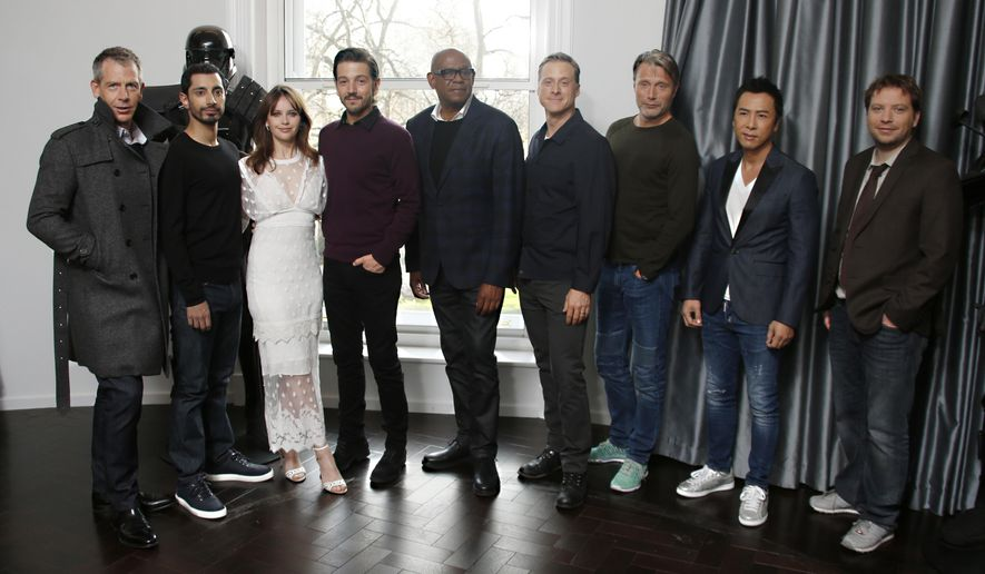 Actors from left, Ben Mendelsohn, Riz Ahmed, Felicity Jones, Diego Luna, Forest Whitaker, Alan Tudyk, Mads Mikkelsen, Donnie Yen and director Gareth Edwards pose for photographers during the Rogue One: A Star Wars Story fan photo call in London, Wednesday, Dec. 14, 2016. (Photo by Joel Ryan/Invision/AP)