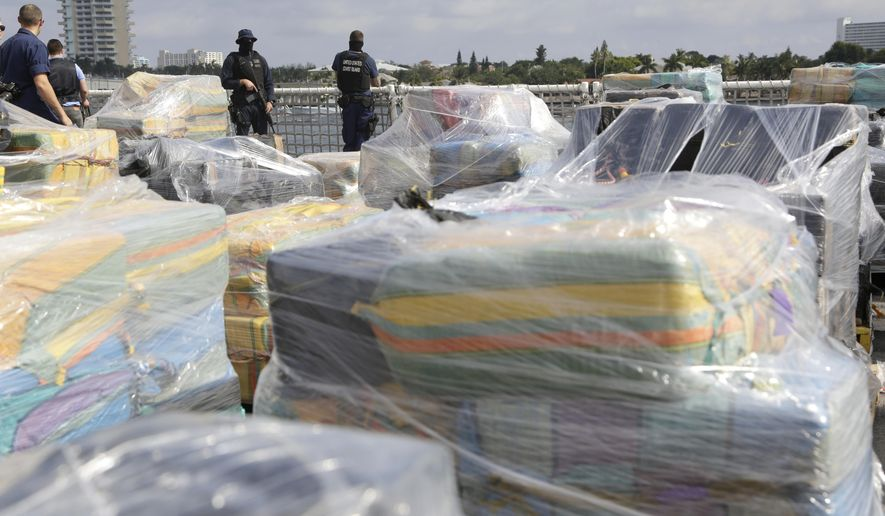 Coast Guardsmen stand over pallets containing more than 26 tons of cocaine worth at least $715 million, on the flight deck of of 418-foot Coast Guard Cutter Hamilton, Thursday, Dec. 15, 2016, in Fort Lauderdale, Fla. The cocaine was brought ashore Thursday following multiple recent seizures by the U.S. Coast Guard and the Royal Canadian Navy in the eastern Pacific. (AP Photo/Lynne Sladky)