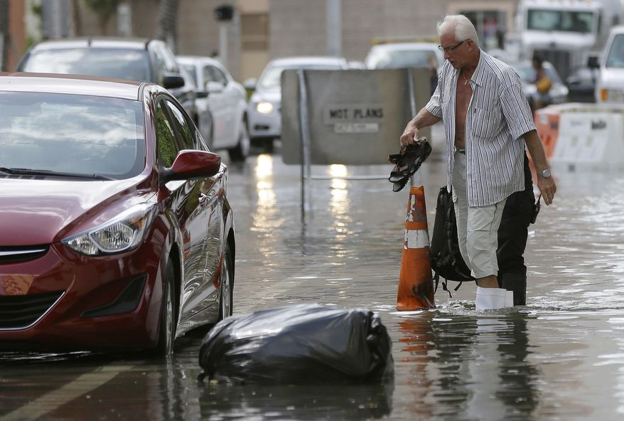 FILE - In this Sept. 30, 2015 file photo, a hotel guest carries his shoes as he is escorted to his car along in Miami Beach, Fla. The street flooding was in part caused by high tides due to the lunar cycle, according to the National Weather Service. A new scientific report finds man-made climate change played some kind of role in two dozen extreme weather events around the world in 2015. But it also detected no global warming fingerprints in a handful of other weird weather instances. (AP Photo/Lynne Sladky, File)