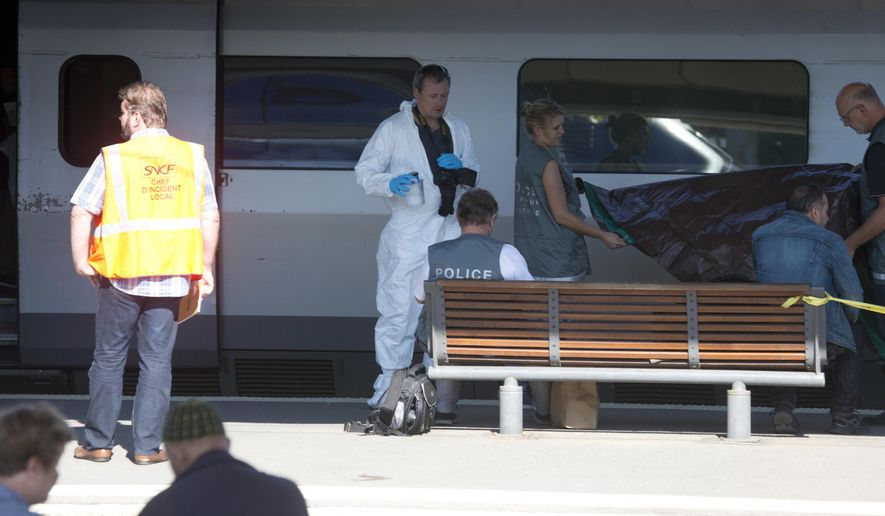 FILE - In this Aug. 22 2015 file photo, members of the police forensics team take part in an investigation next to a Thalys train on the platform at Arras train station, northern France. The main suspect in the case of a high-speed train attack thwarted by three Americans last year in northern France will be questioned by counter-terrorism judges Wednesday Dec. 14, 2016 in Paris. (AP Photo/Virginia Mayo, File)