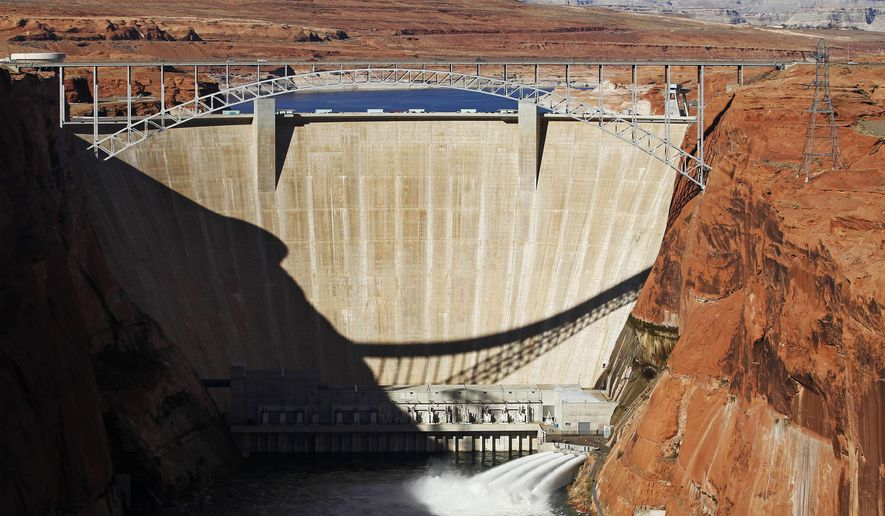 FILE - This Nov. 19, 2012, file photo, shows the high-flow release of water into the Colorado River from bypass tubes at Glen Canyon Dam in Page, Ariz. The federal government is committing another 20 years to the aging and embattled Glen Canyon Dam  it calls crucial to water and power supplies in the West, but that critics say is unstable and should be ripped down. U.S. Interior Secretary Sally Jewell signed documents at a regional water conference Thursday, Dec. 15, 2016, in Las Vegas to have the federal Bureau of Reclamation continue to manage Glen Canyon Dam through 2036. (Rob Schumacher/The Arizona Republic via AP, File)