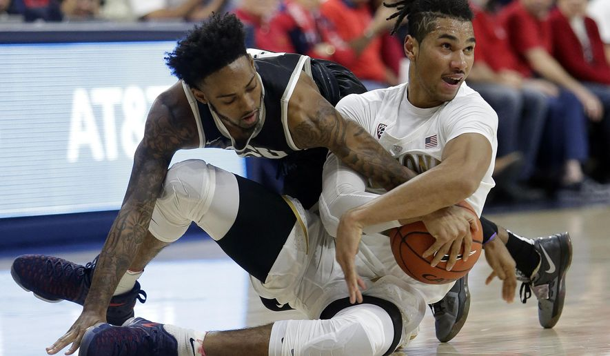 Grand Canyon guard Shaq Carr, left, and Arizona forward Keanu Pinder battle for a loose ball during the first half of an NCAA college basketball game, Wednesday, Dec. 14, 2016, in Tucson, Ariz. (AP Photo/Rick Scuteri)