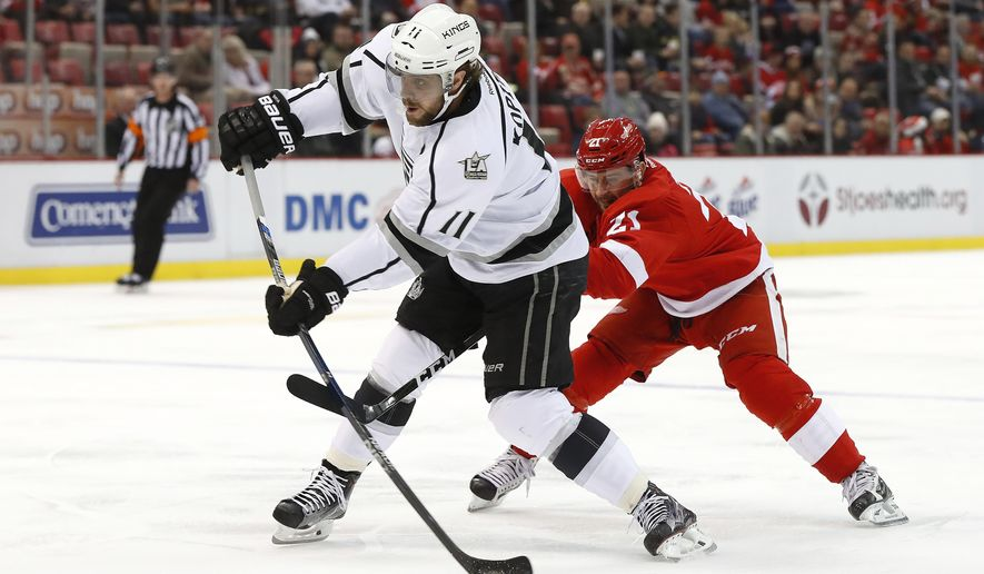 Los Angeles Kings center Anze Kopitar (11) shoots as Detroit Red Wings left wing Tomas Tatar (21) defends in the first period of an NHL hockey game Thursday, Dec. 15, 2016, in Detroit. (AP Photo/Paul Sancya)