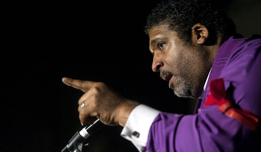 "FILE - In this Nov. 29, 2016 file photo, The Rev. Dr. William Barber, President of the North Carolina NAACP, addresses a crowd during a ""Fight for 15"" rally in Durham, NC. The leader of North Carolina's ""Moral Monday"" progressive movement and the state's NAACP is suing American Airlines saying he was removed from a flight because he is black. News outlets report that Barber filed a federal lawsuit Wednesday, Dec. 14 in Alexandria, Va., demanding unspecified monetary damages and changes at the airline. (Kaitlin McKeown  /The Herald-Sun via AP, File)"