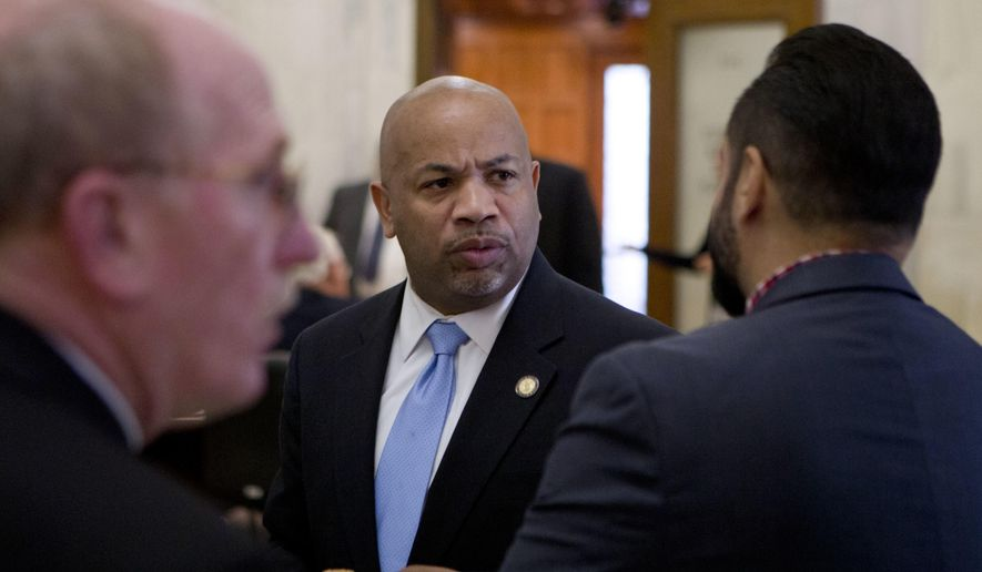 FILE- In this May 3, 2016 file photo, New York State Assembly Speaker Carl Heastie, D-Bronx, talks with colleagues in a hallway near the Assembly Chamber at the state Capitol in Albany, N.Y. Heastie leads the Democrats in the New York Legislature who are seeking a pay raise. They haven't seen an increase in 17 years, and many say the salary hasn't kept up. (AP Photo/Mike Groll, File)