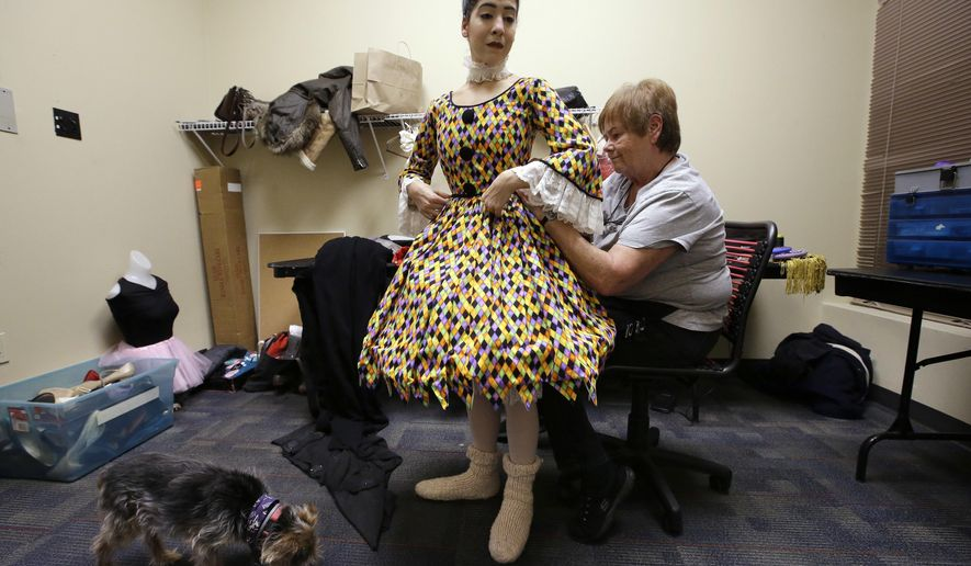 In this Wednesday, Dec. 14, 2016 photo Festival Ballet Providence company dancer Jennifer Ricci, is assisted with her Nutcracker ballet Columbine Doll costume by seamstress Helen Ferreira, right, in a fitting room backstage at the Providence Performing Arts Center, in Providence, R.I. Following the theft, discovered in November of 2016, of many of the company's costumes, ballet companies from a number of states across the country reached out to offer help and sent costumes to Providence for the Nutcracker performances. The Columbine Doll costume was sent from Mobile Ballet, in Mobile, Ala. (AP Photo/Steven Senne)