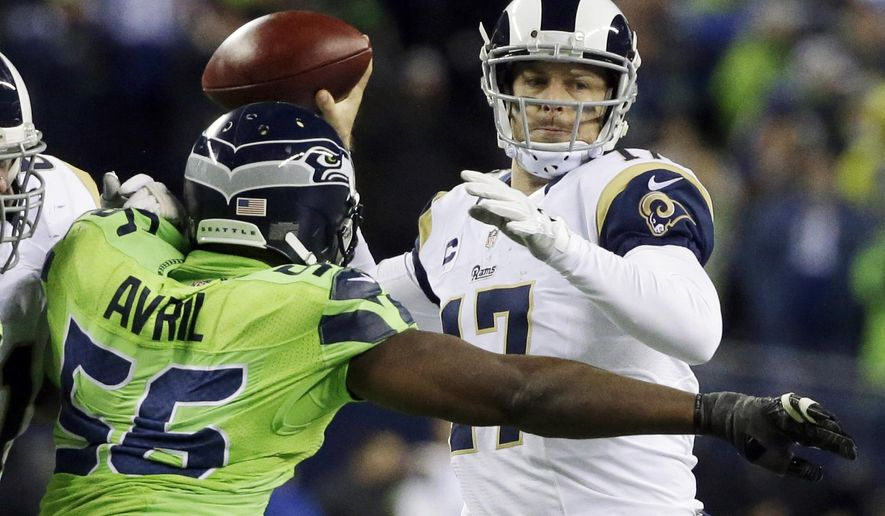 Los Angeles Rams backup quarterback Case Keenum passes under pressure from Seattle Seahawks defensive end Cliff Avril (56) in the second half of an NFL football game, Thursday, Dec. 15, 2016, in Seattle. (AP Photo/Elaine Thompson)