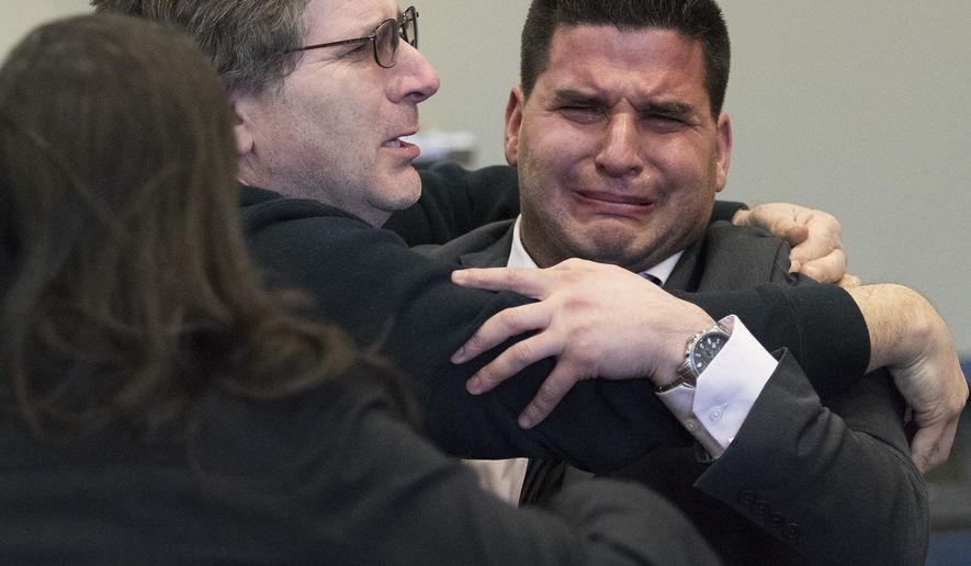 Andrew Rifkin, right, is greeted with hugs by his father, Steve, as twin sister Ashley, left, breaks into tears moments after hearing Judge William Brady announce the jury's verdict of not guilty during Andrew Rifkin's trial at the DeKalb County Courthouse in Sycamore, Ill., on Thursday, Dec. 15, 2016. Rifkin, 28, was accused of performing a specific sex act against the will of a female former NIU student while he was working as a NIU police officer. (Matthew Apgar/Daily Chronicle via AP)