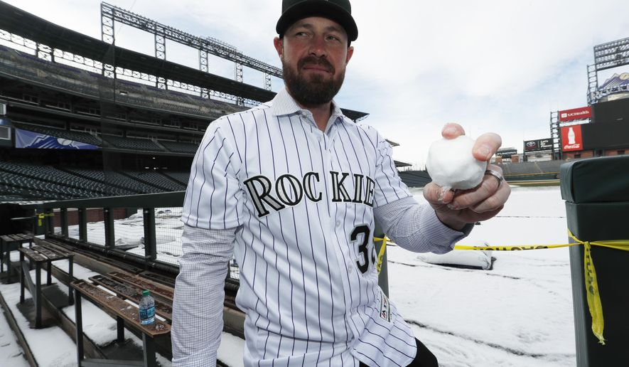 Newly signed Colorado Rockies relief pitcher Mike Dunn holds up a snowball that he fashioned out of the light snow cover in front of the team's dugout in Coors Field after he was introduced at a news conference by the team Thursday, Dec. 15, 2016, in Denver. (AP Photo/David Zalubowski)